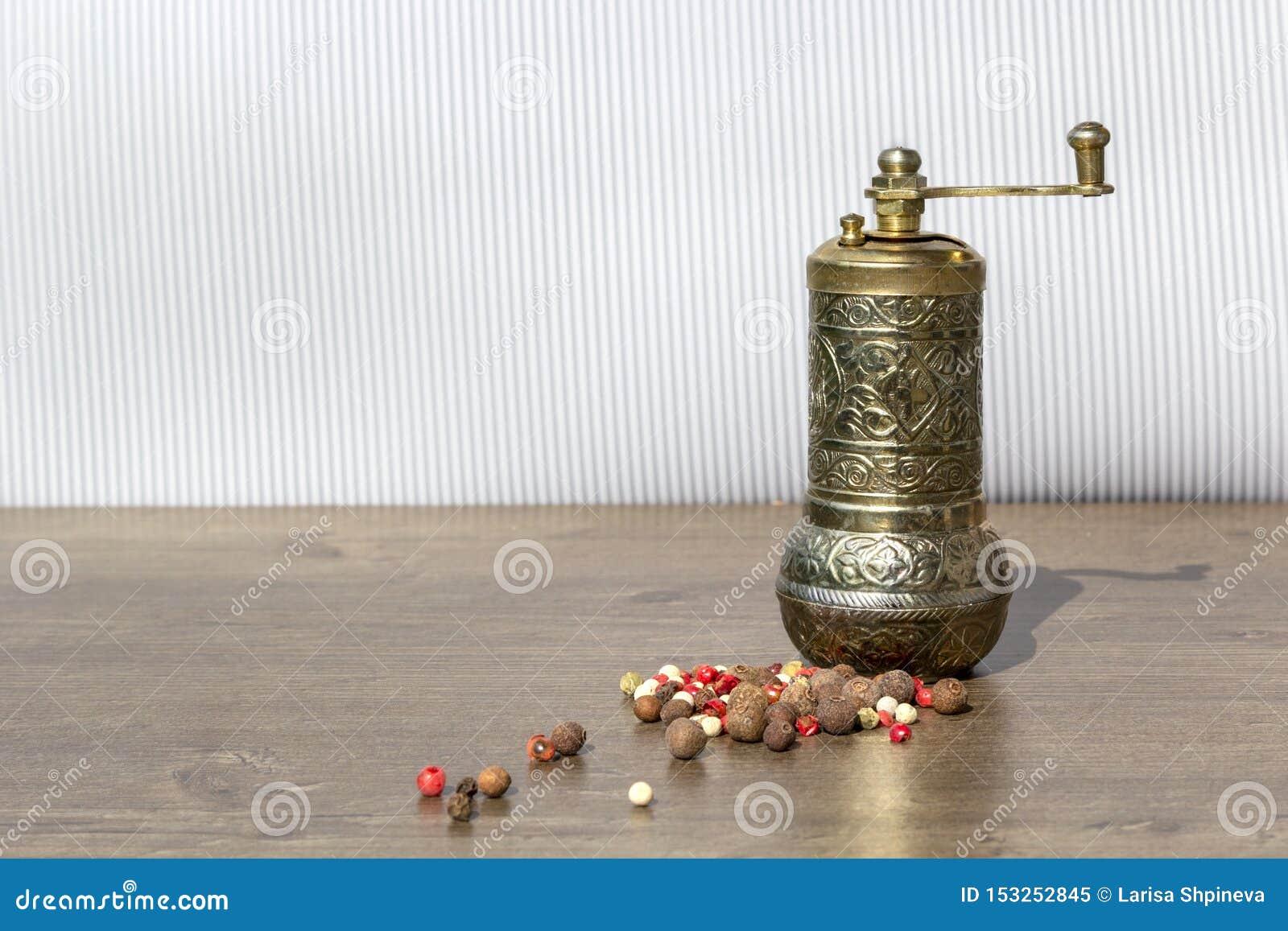 Moinho do vintage para a pimenta com grãos de pimenta e pimenta da Jamaica pretos na tabela de madeira Dispositivos de cozinha pa