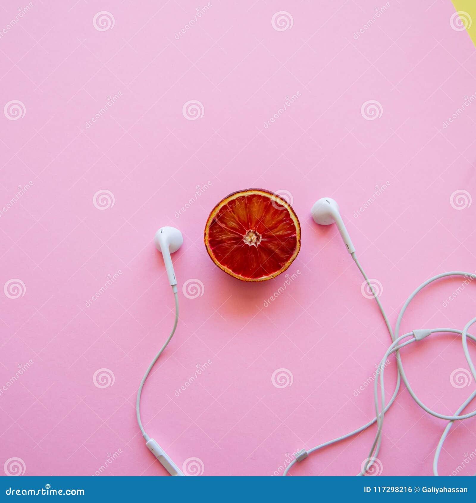 Moitié d orange sanguine et d écouteurs sur un fond rose place