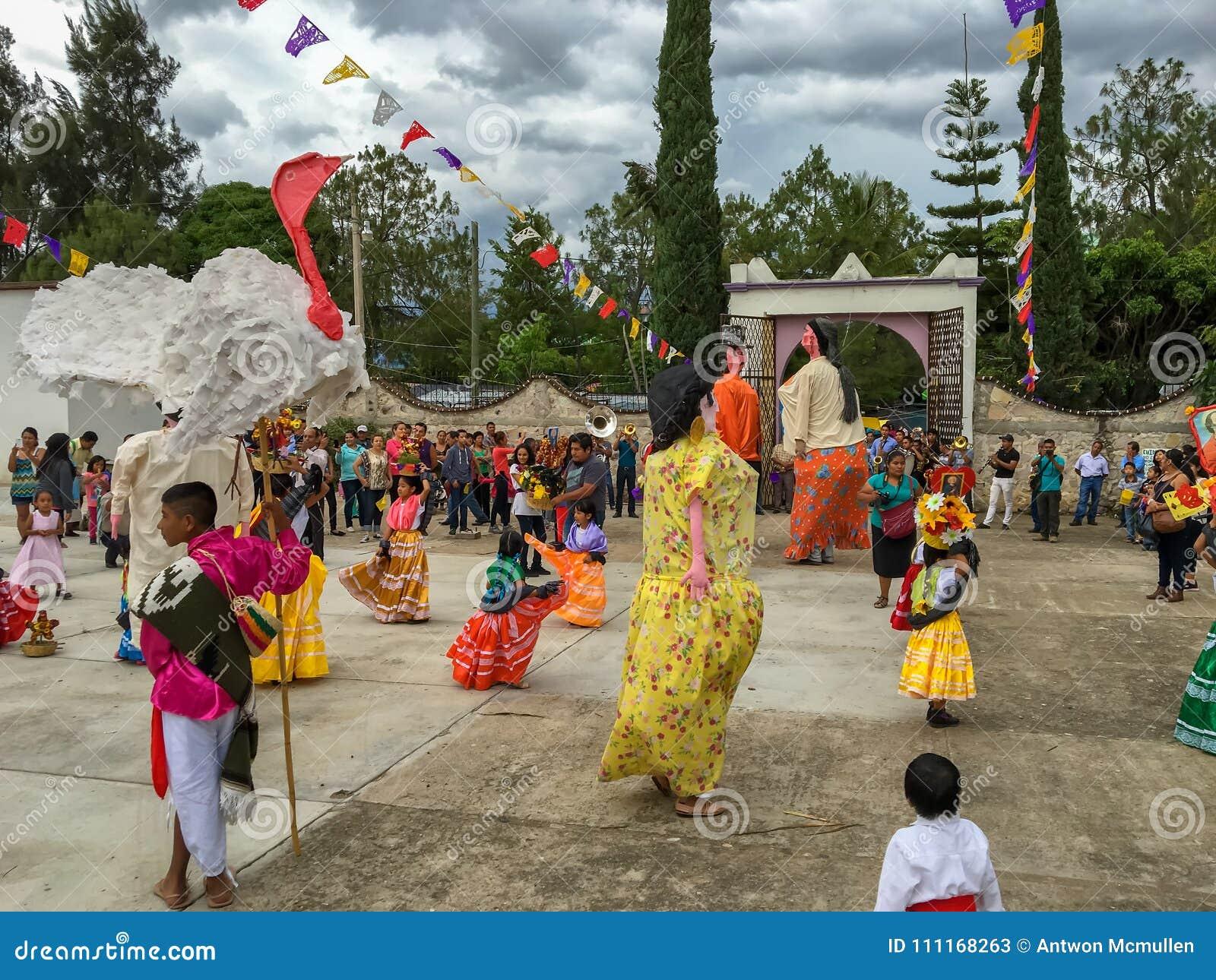 Mojigangas e crianças que dançam em Calenda San Pedro em Oaxaca
