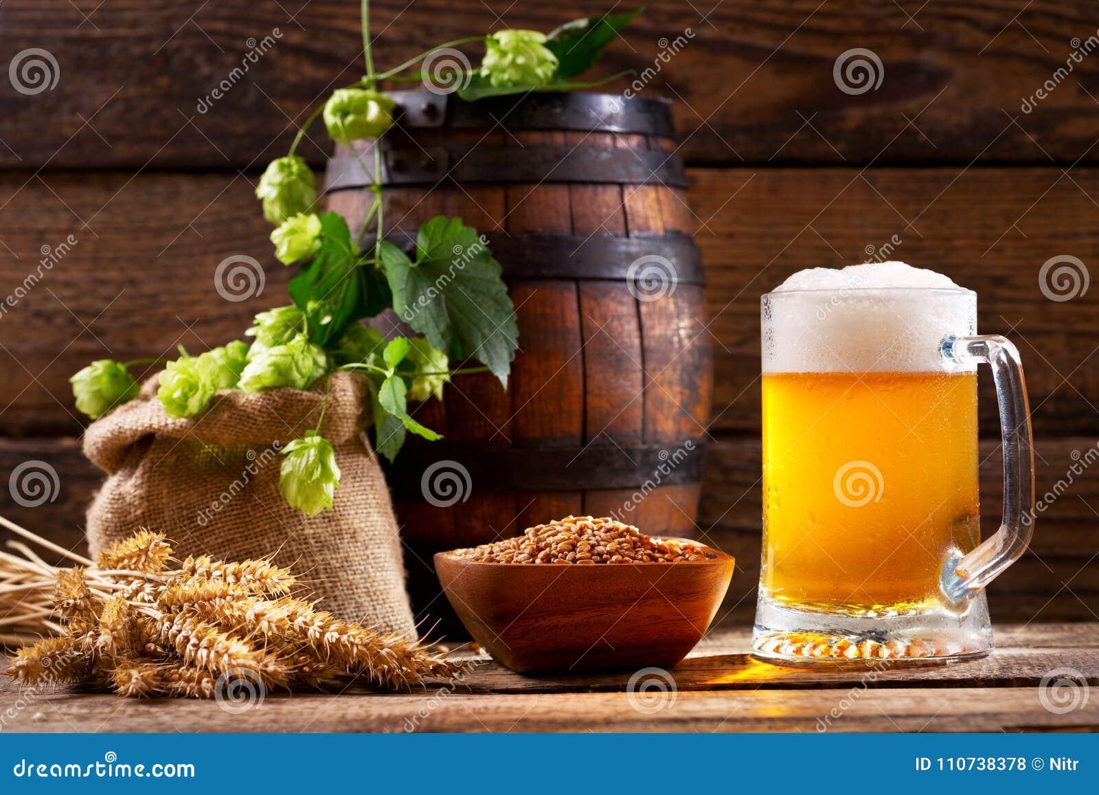 Mok bier met groene hop, tarweoren en houten vat