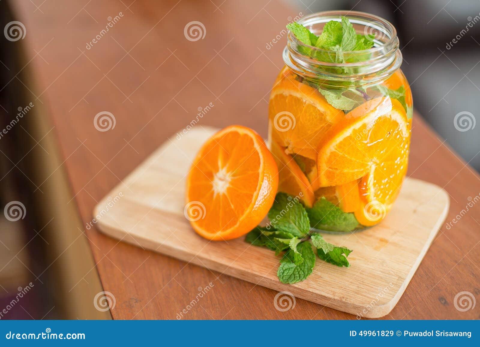 Mok heerlijke verfrissende drank van oranje fruit, gegoten water
