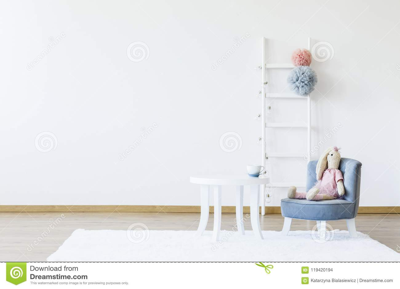Mokiet zabawka na popielatym krześle przy bielu stołem w minimalnym dziecka ` s pokoju ja