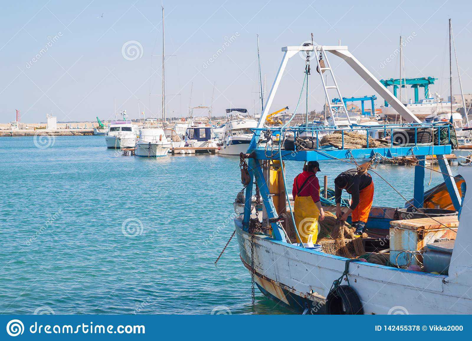 Fishermen on boat with fishing nets