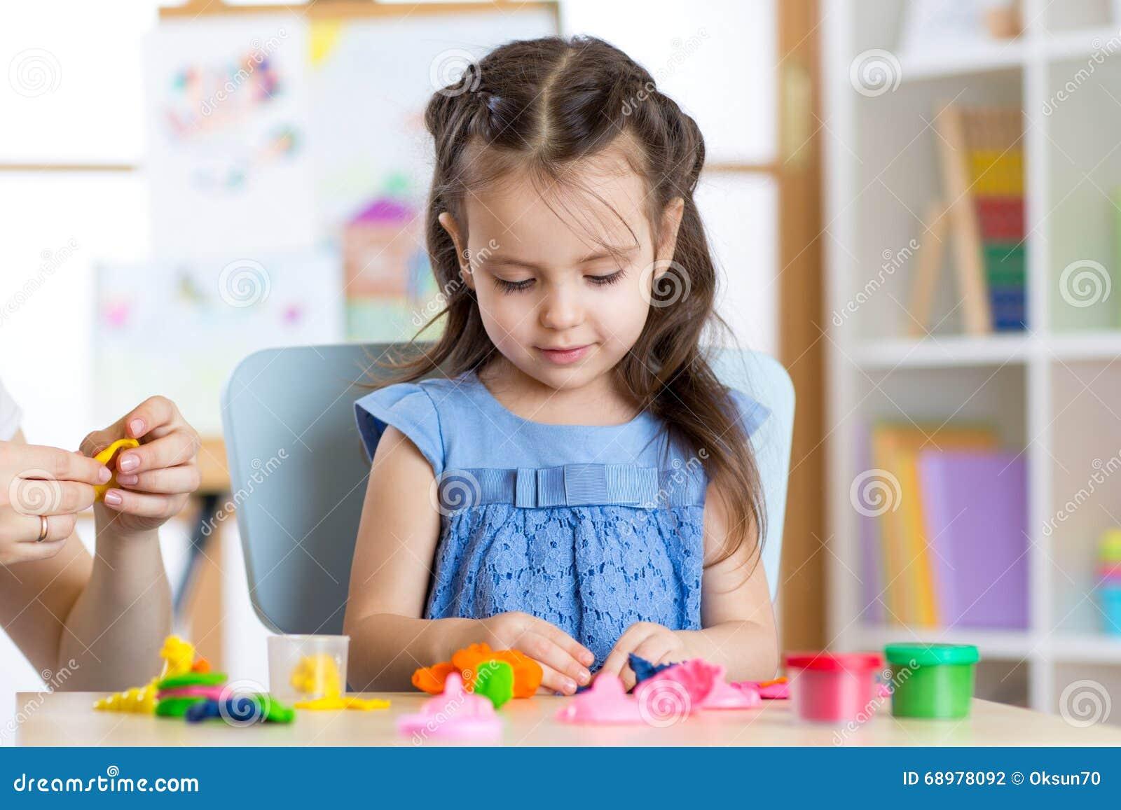Moldes lindos de la niña del plasticine en la tabla