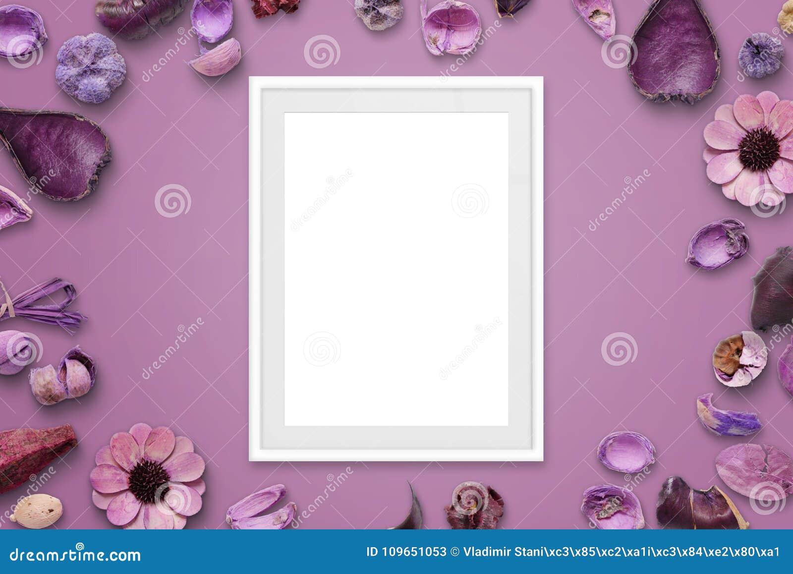 Moldura para retrato branca no fundo cor-de-rosa cercado com decorações da flor