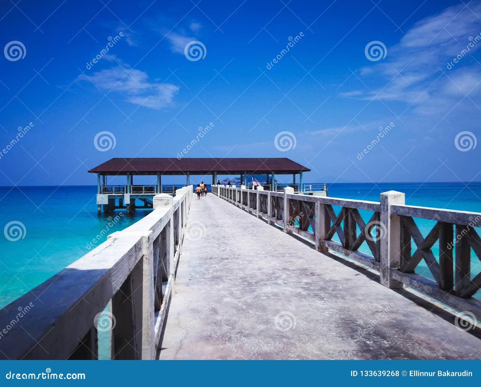 Molhe de madeira no meio-dia sob céus azuis claros com passeio dos povos
