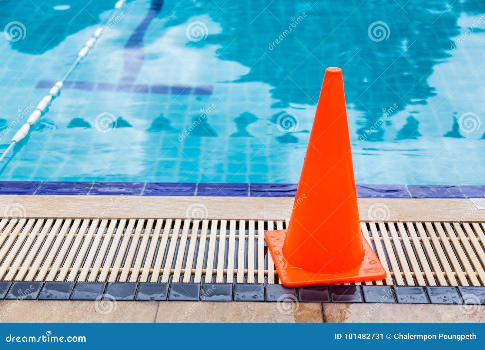 Molhe o cone alaranjado brilhante colocado pelo lado da piscina como o safet