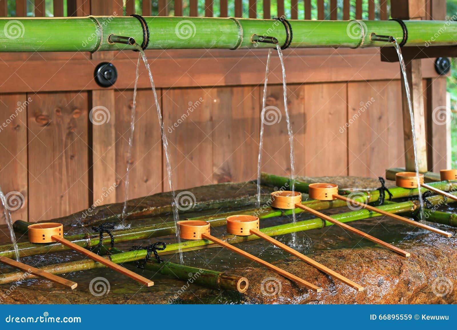 Molhe o corredor para fora através da tubulação de bambu para molhar a bacia em Shimogam