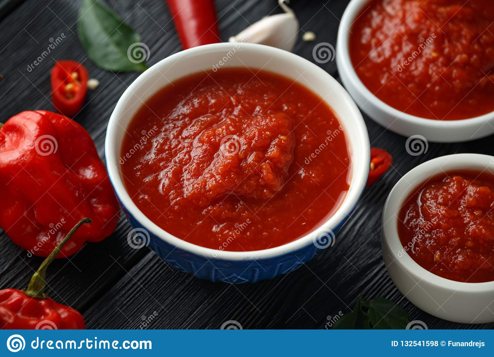 Molho de pimentão doce quente picante com mistura de pimenta, de alho e de tomates no fundo de madeira rústico