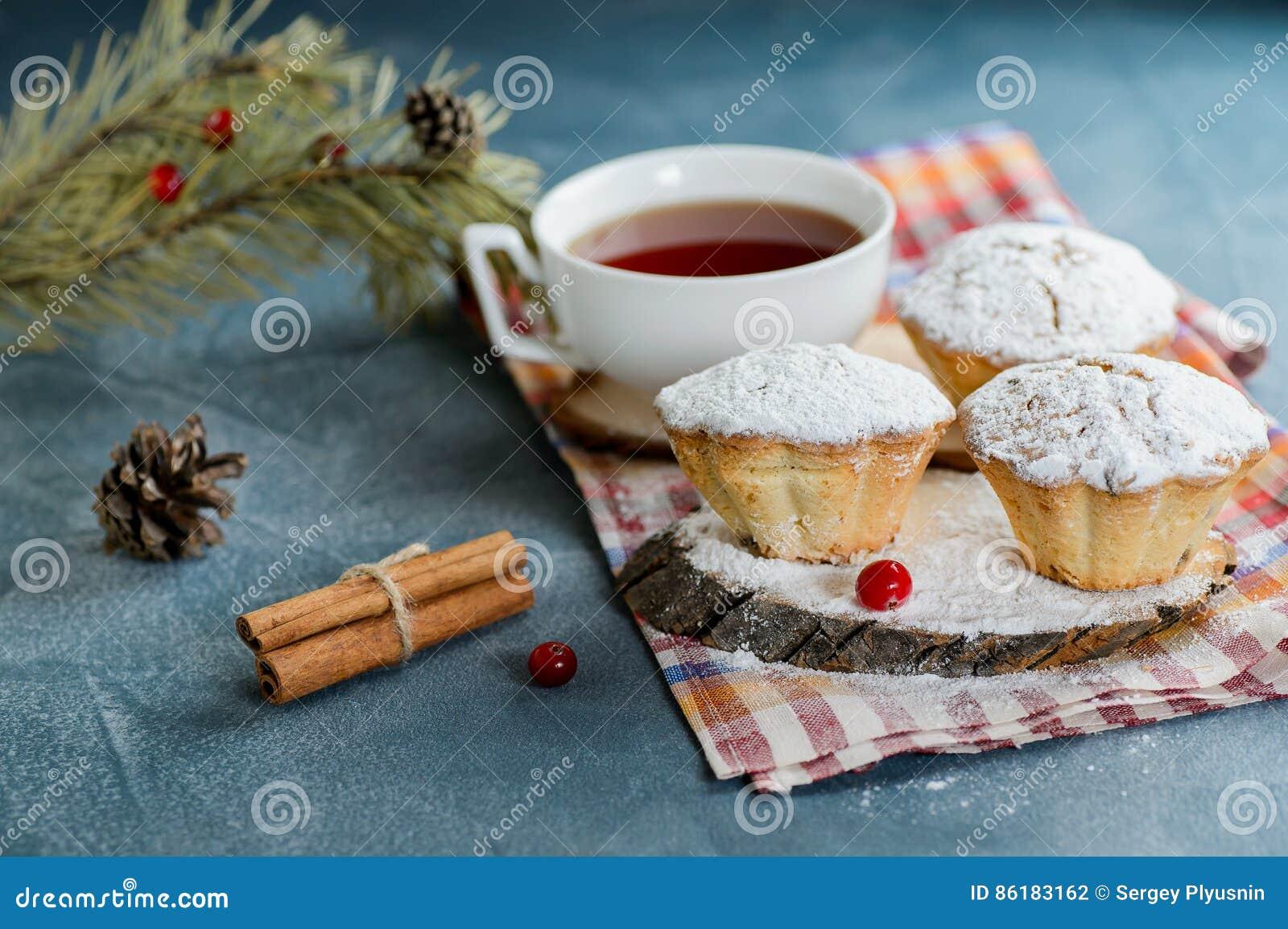 Molletes hechos en casa frescos del arándano en azúcar de formación de hielo con las ramas y el té del abeto