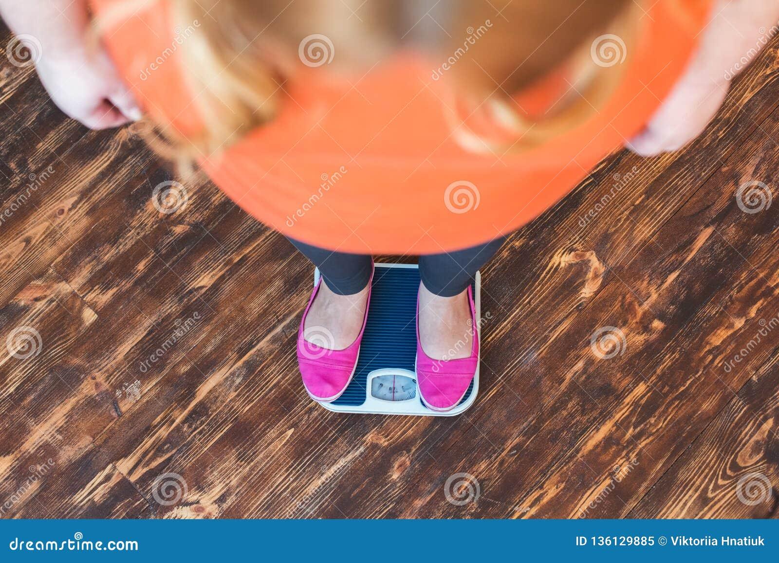 Mollige vrouwensport die zich thuis het bekijken close-up van de schalen het hoogste mening bevinden