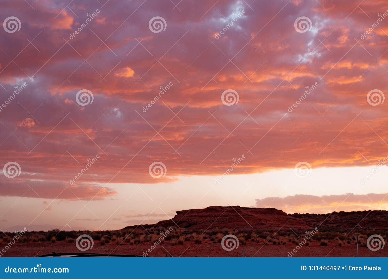 Moln i en röd kulör solnedgång i den Colorado ökenplatån på Tuba City, Förenta staterna