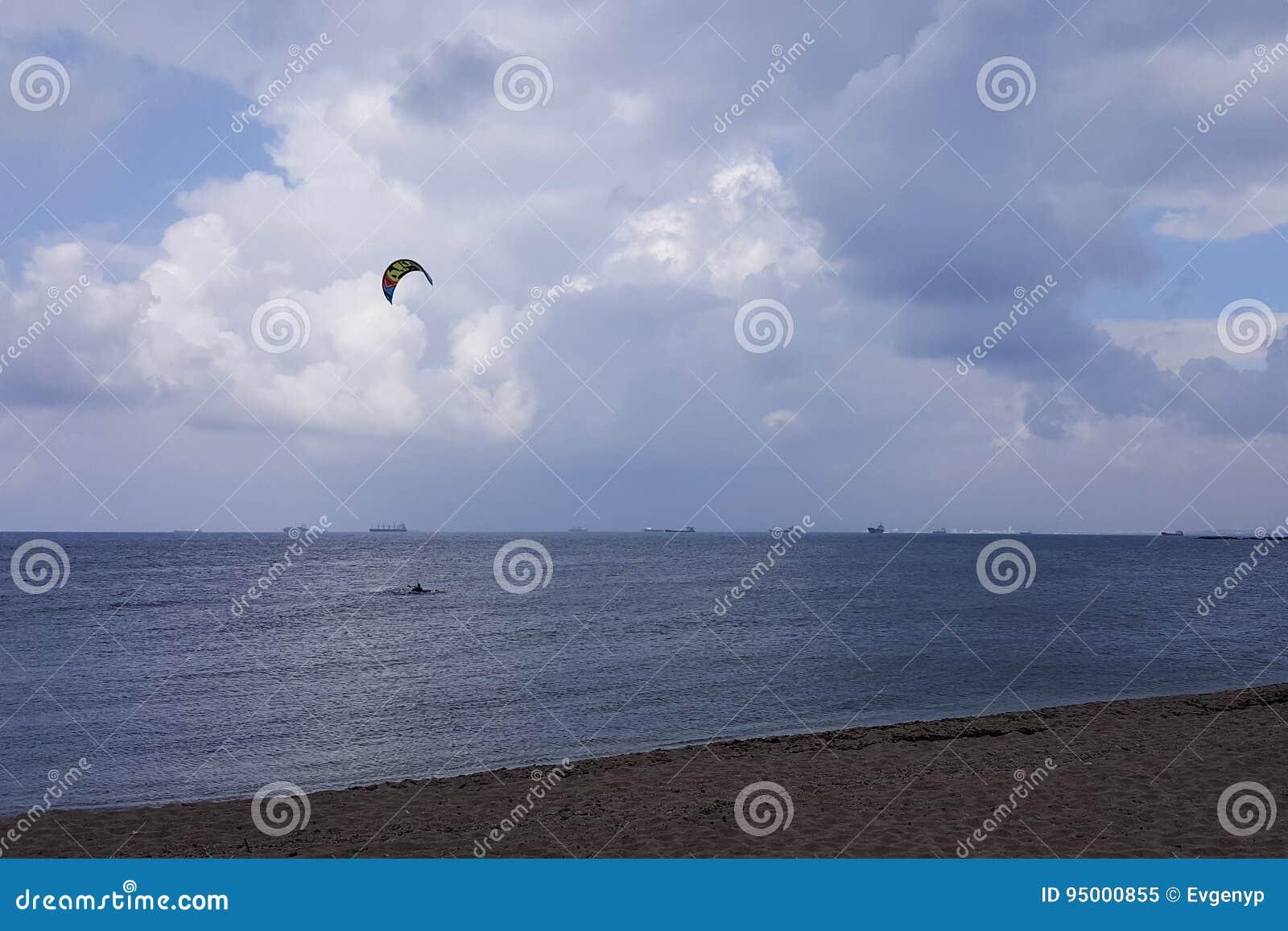 Molnigt väder på kusten, surfare rider i regnet som hänger fördunklar