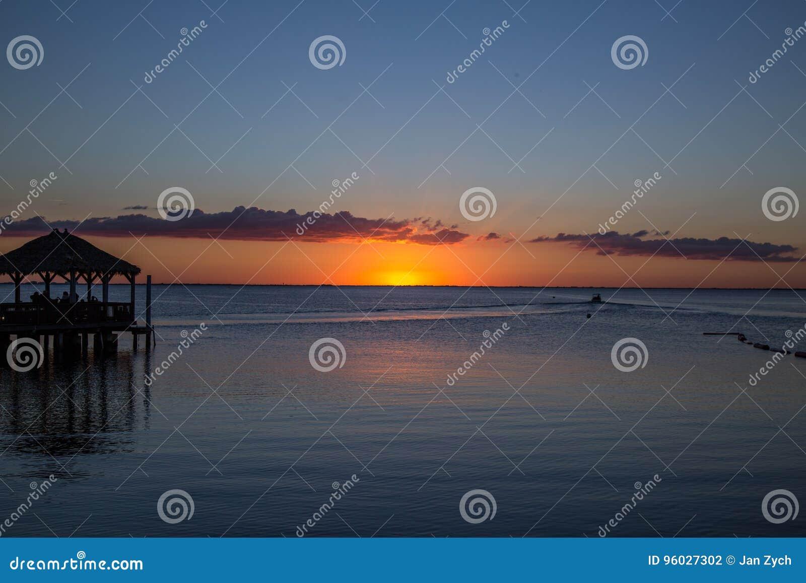 Molo, łódź zmierzch i morze, i