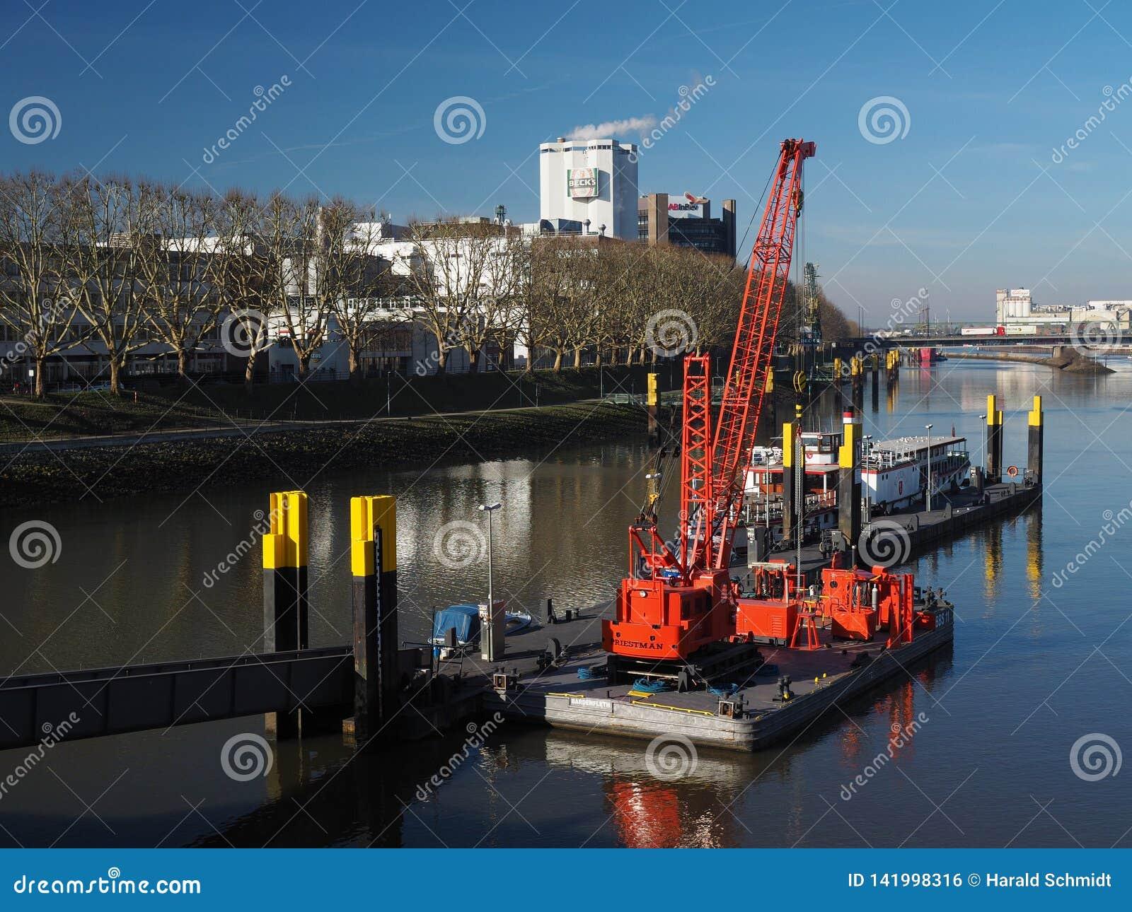Molo z kilka małymi naczyniami i jaskrawy czerwony spławowy linia horyzontu z Beck żurawia i miasta «Bremen, Niemcy, Luty - 14th,