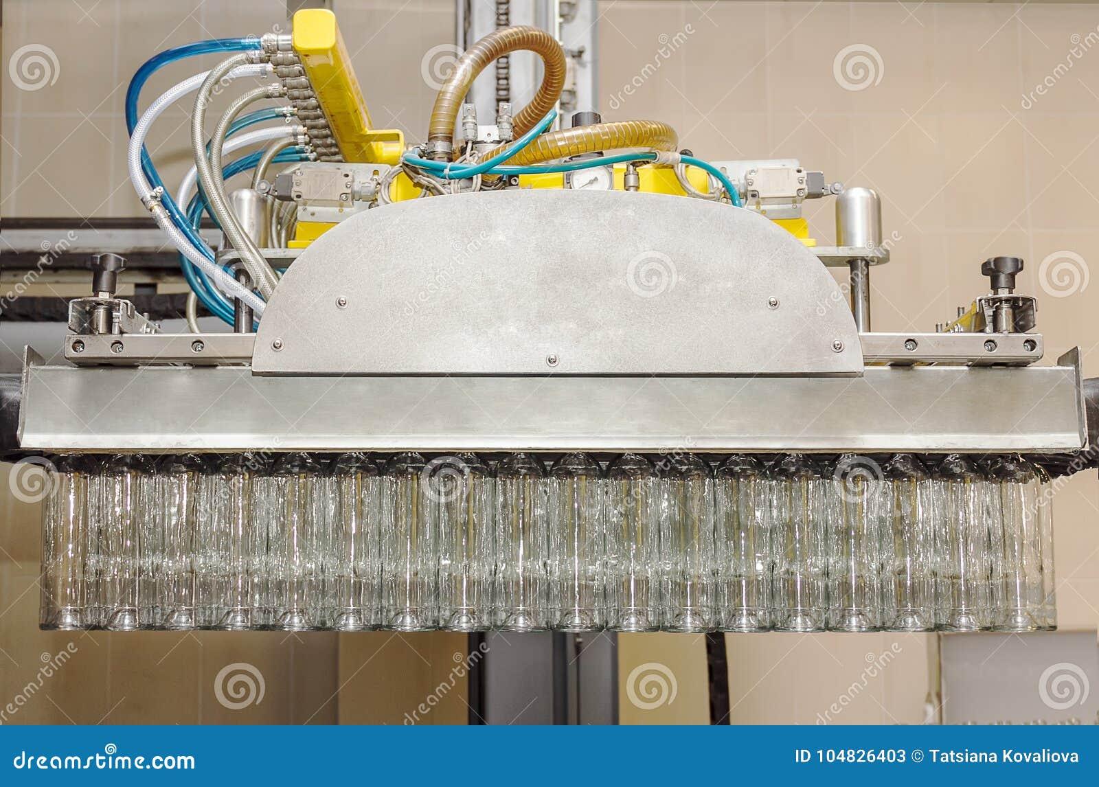 Molte bottiglie di vetro che appendono in una pinza di presa pneumatica Bottiglie di vetro di carico dai pallet