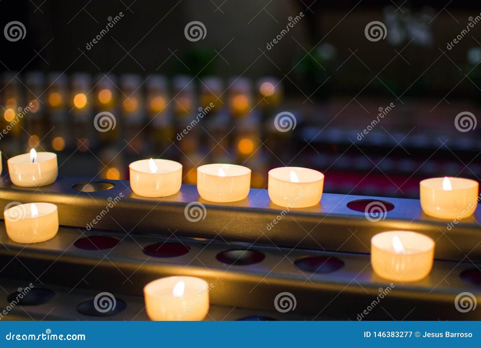 Molte candele brucianti con profondità di campo bassa e fondo defocused