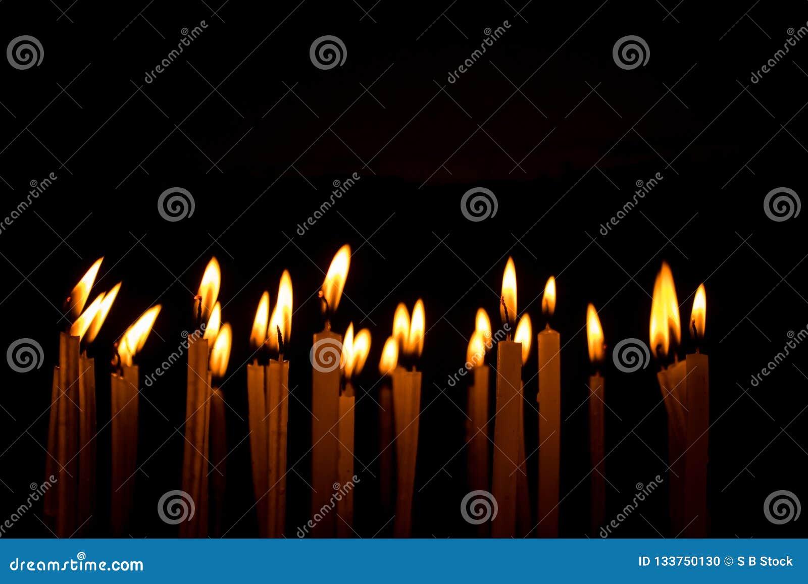 Molte candele di natale che bruciano alla notte sui precedenti neri