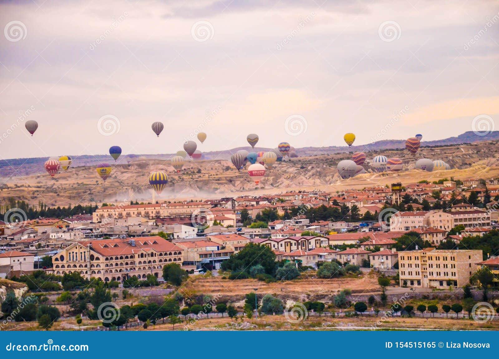 Molte mongolfiere che sorvolano paesaggio roccioso nella città di Goreme a Cappadocia