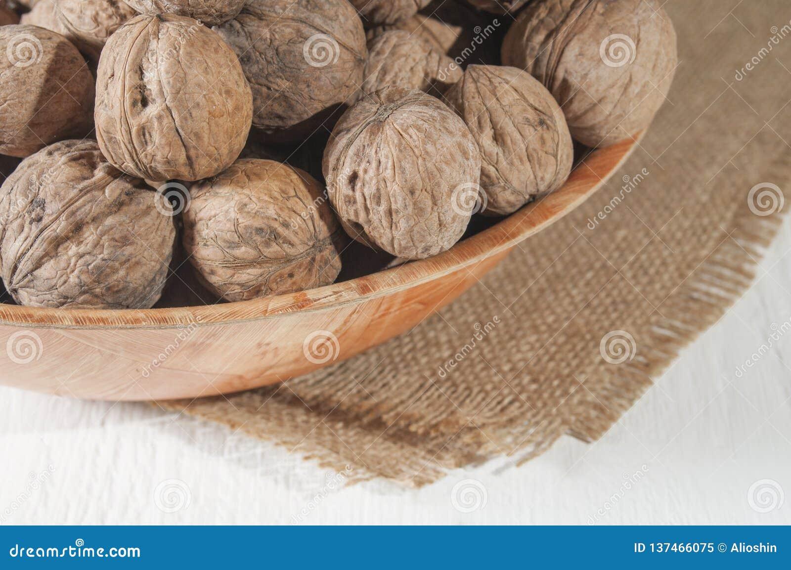Molte noci si trovano in una ciotola Ciotola su tela da imballaggio Tabella di legno bianca