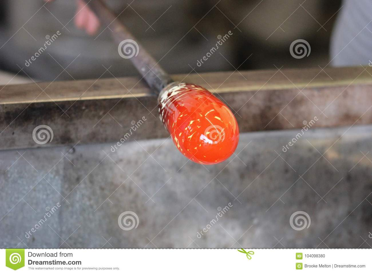 Molten glass on a metal rod for glass blowing macro