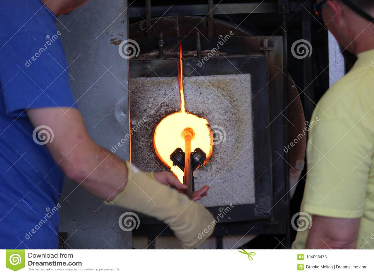 Molten glass on a metal rod in a furnace for glass blowing macro