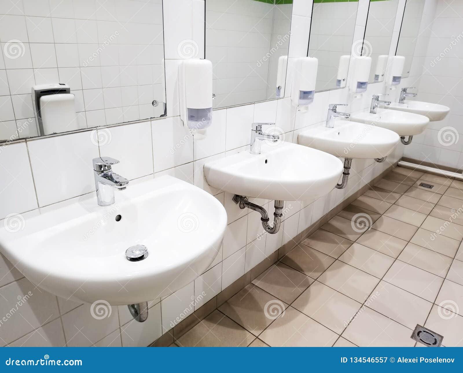 Molti bacini lavare con gli specchi sulla parete in una toilette pubblica