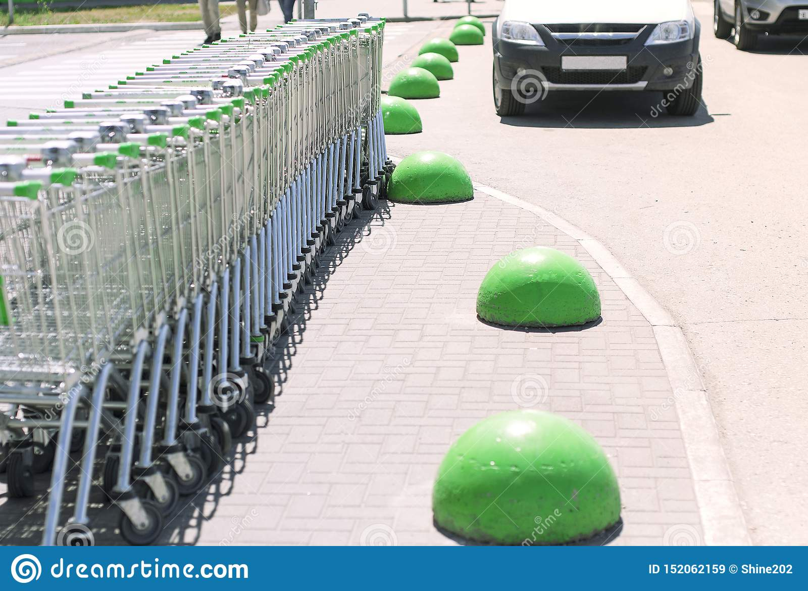 Molti carretti della drogheria parcheggiati vicino al centro commerciale sull asfalto con gli emisferi di pietra verdi