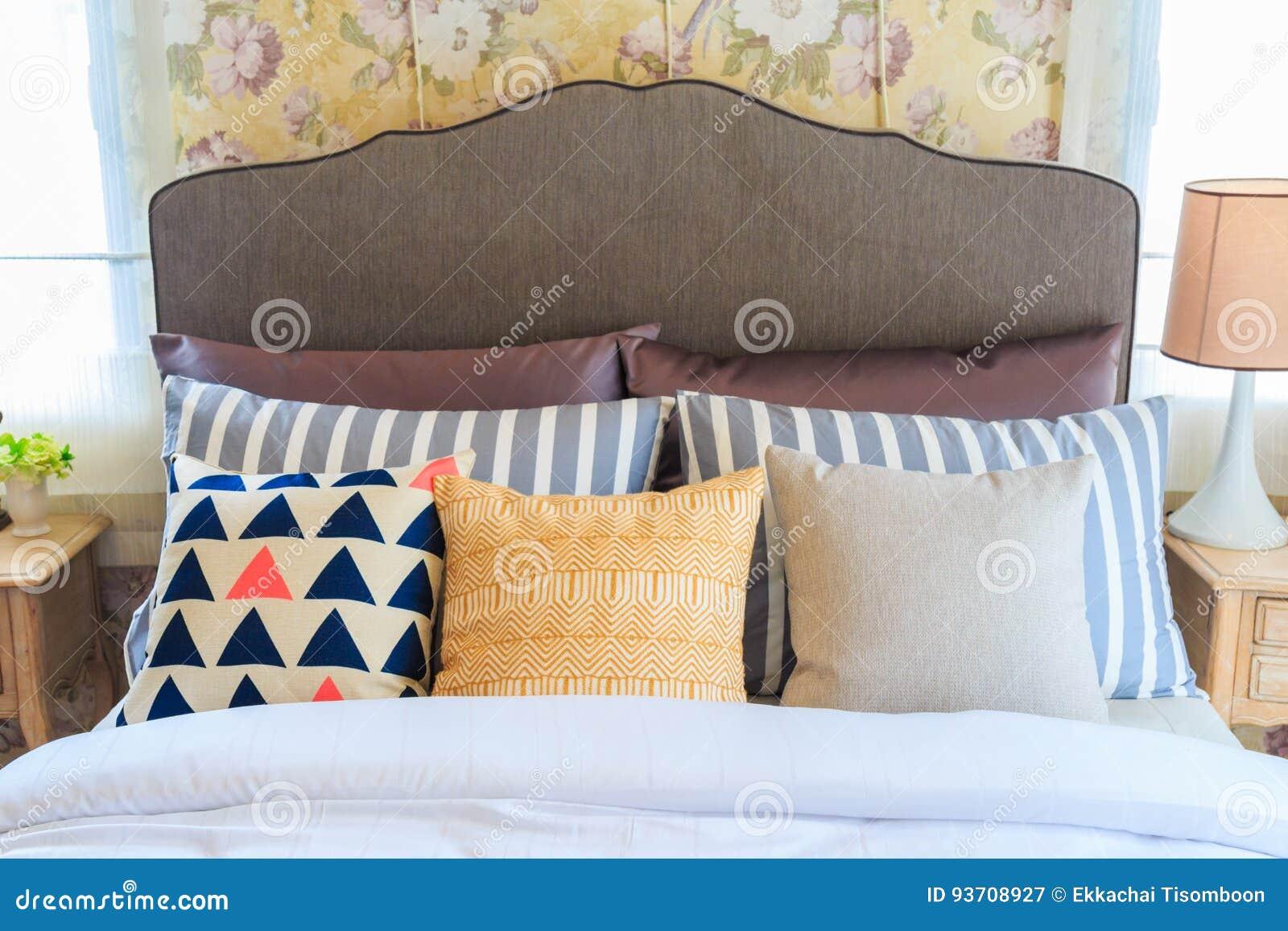 Molti cuscini sul letto e sulle lampade della testata del letto
