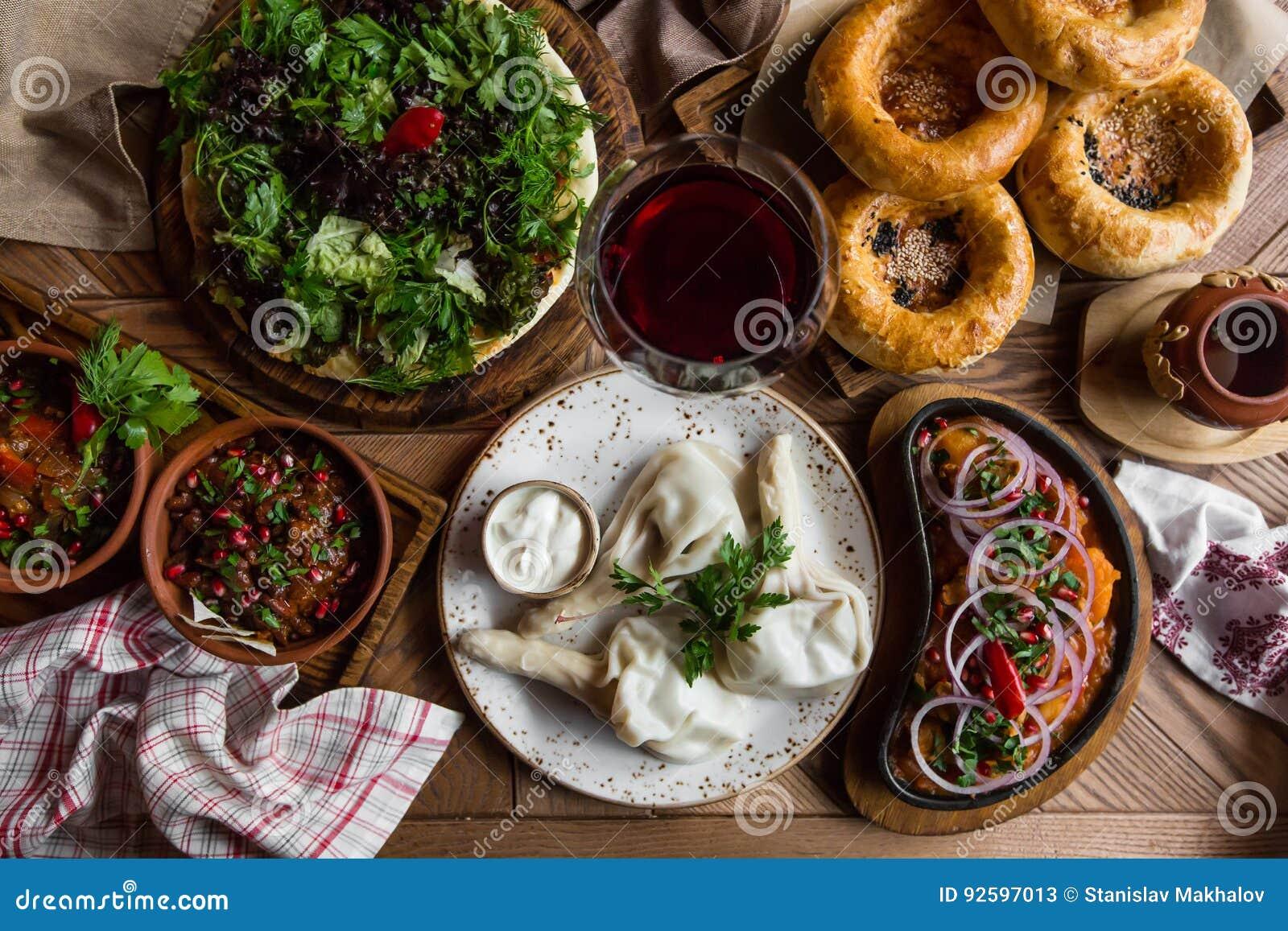 Molto alimento sulla tavola di legno Cucina georgiana Vista superiore Disposizione piana Khinkali e piatti georgiani