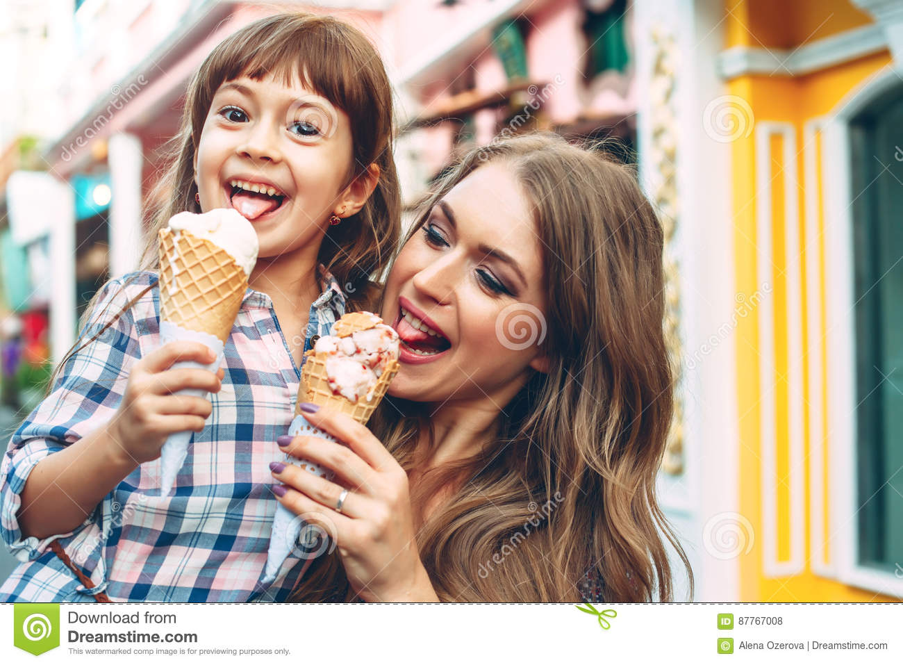 Mom with child eating ice cream in city street