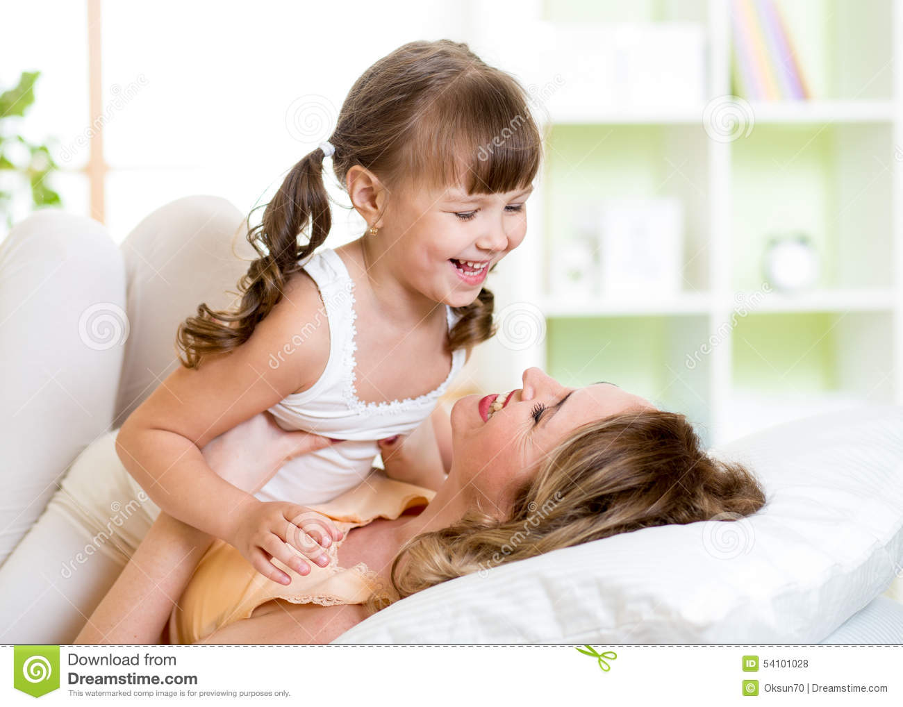 mom and child having fun in bed stock photo - image: 54101028