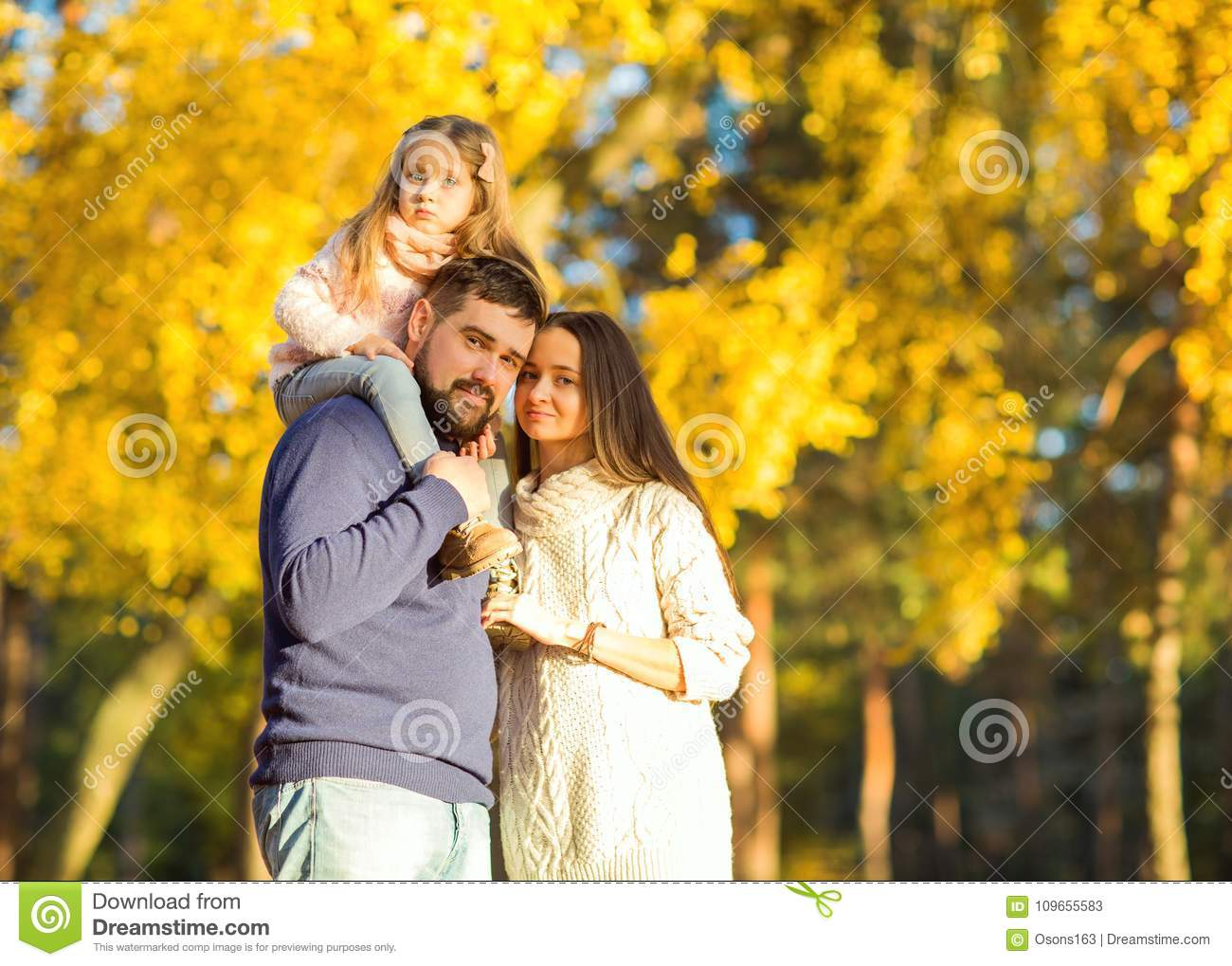 Mom and dad with daughter at sunset in the woods play