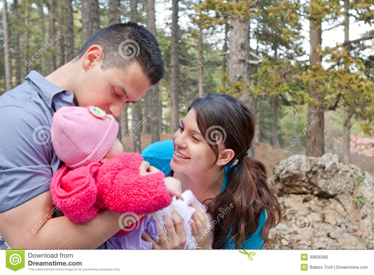 Mom and dad enjoying baby daughter parents playing with and kissing baby girl stock photo