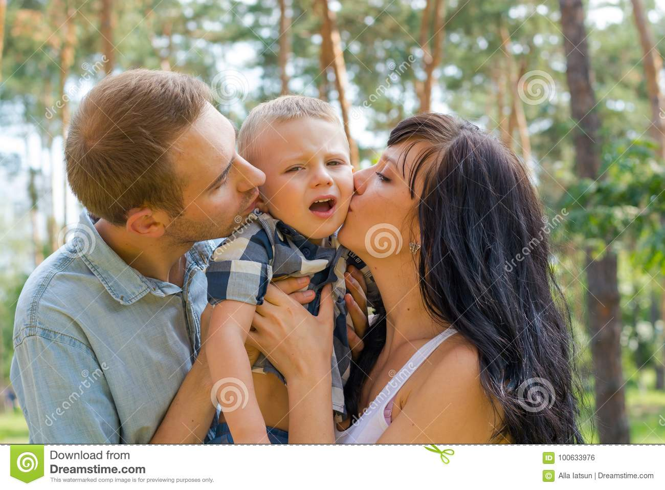 mom and dad hug and kiss their baby, and he`s naughty. stock photo