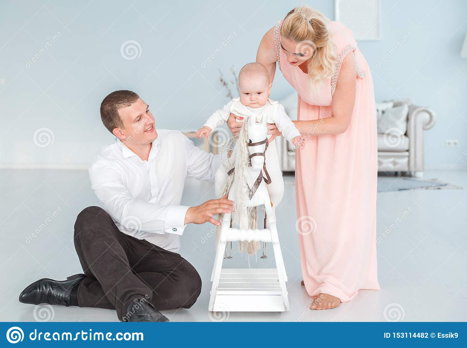 Mom and dad roll their little son on a children`s toy horse