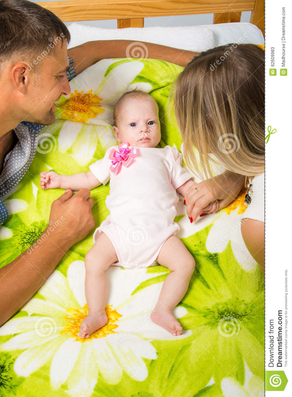 Baby bed next to mom - Mom And Dad Are Sitting Around A Two Month Baby Who Is Lying On The