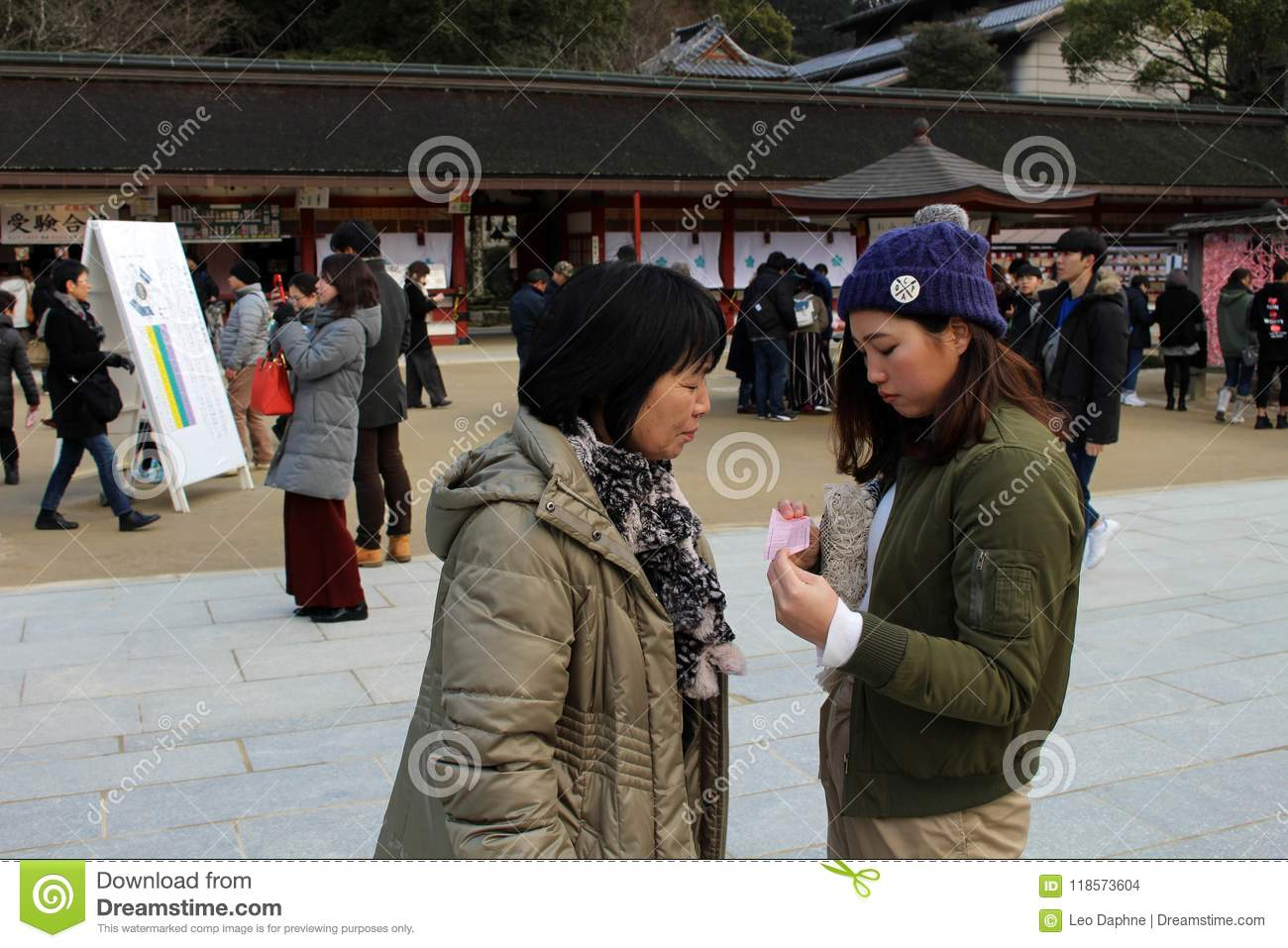 Mom & Daughter Checking The Result Of Fortune-telling Paper