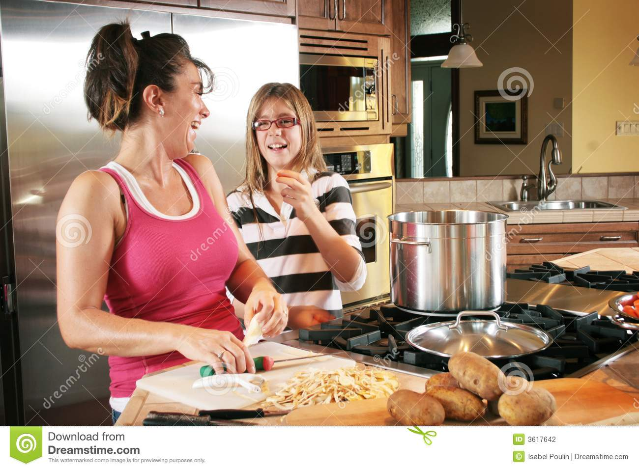 Mother and Daughter in a modern home kitchen, laughing and enjoying ...