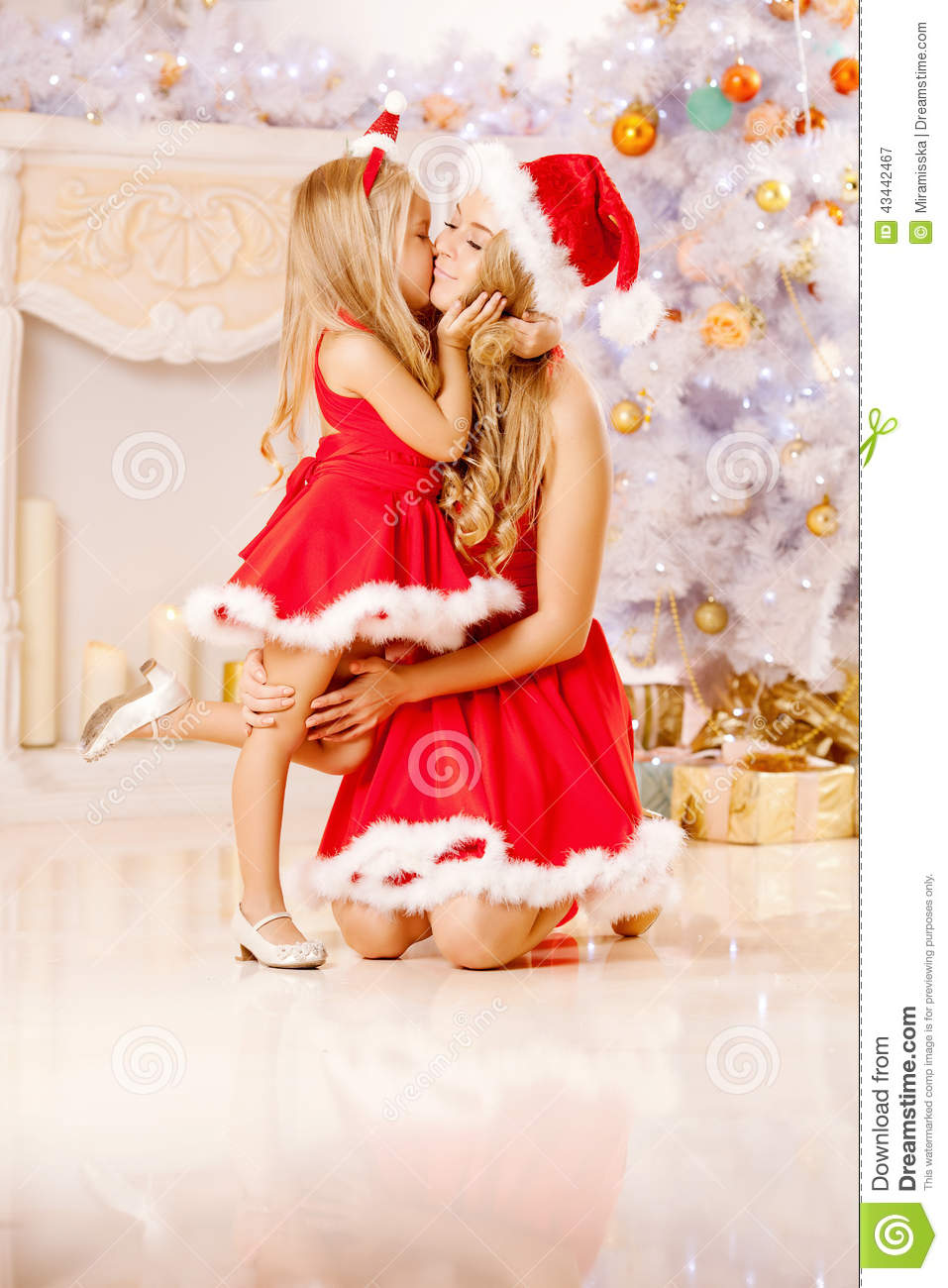 Mom And Daughter Dressed As Santa Celebrate Christmas