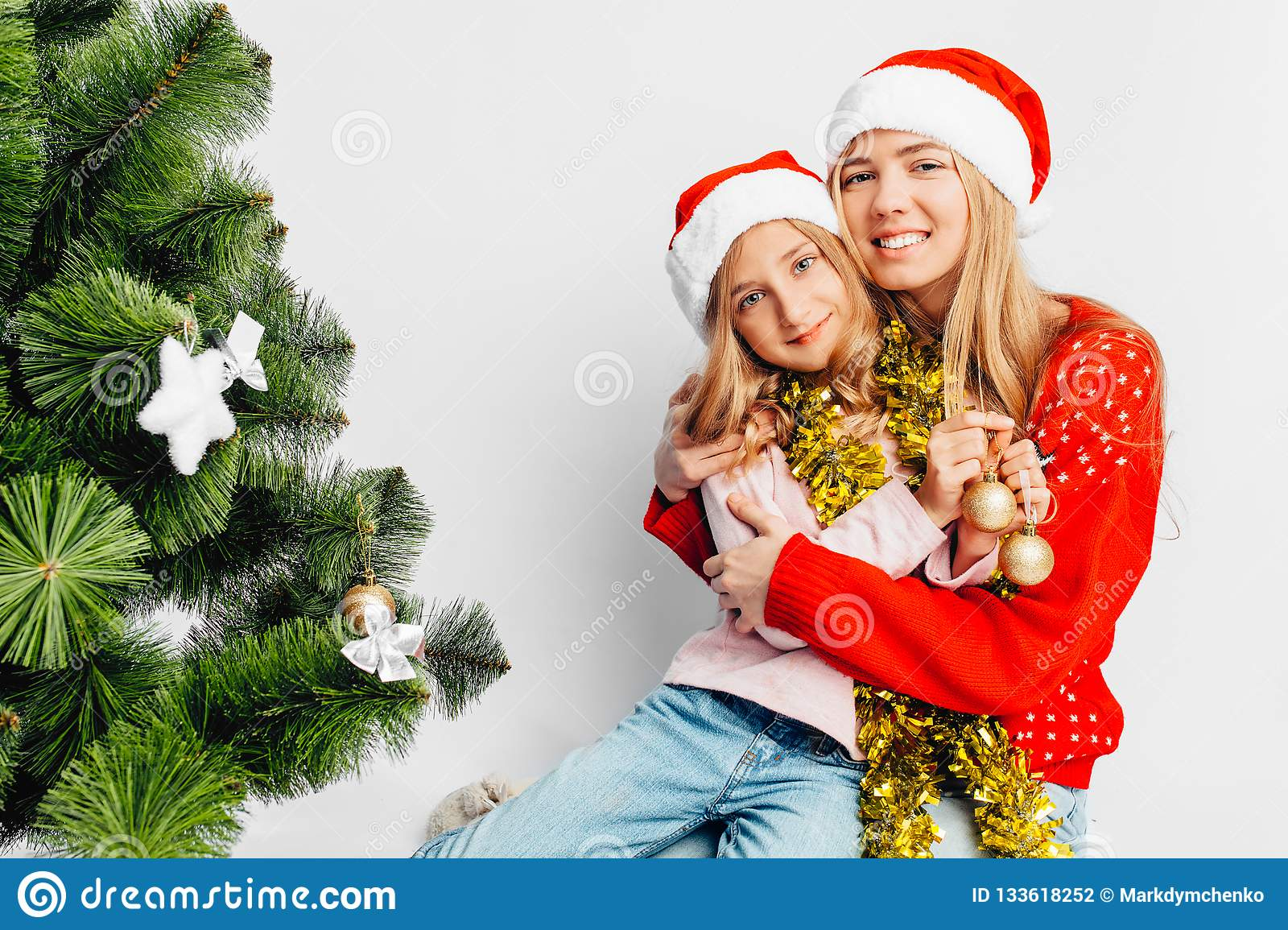 Mom and daughter are dressed in Santa Claus hats, in New Year`s