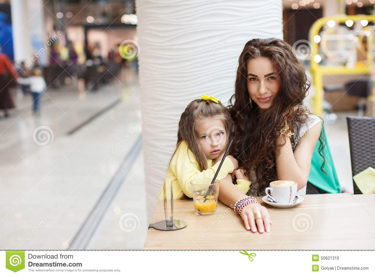 Mom And Daughter Drink Coffee And Juice In A Cafe. Stock ...
