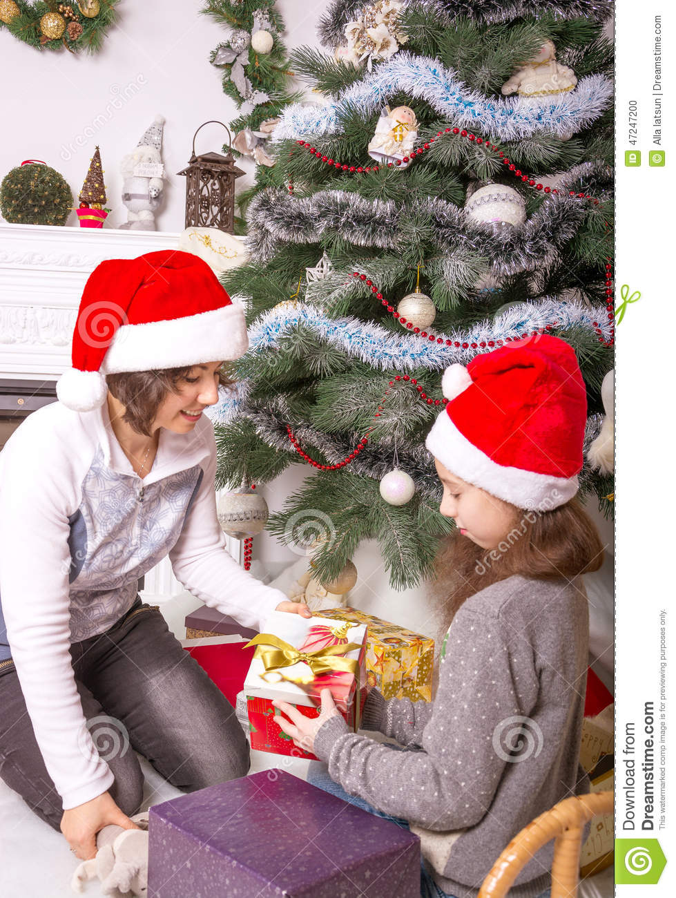 Mom And Daughter With Gifts Under The Christmas Tree