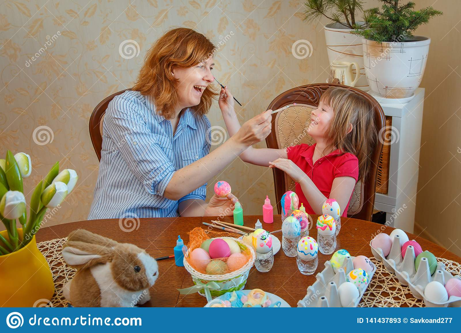 Mom and daughter have fun painting eggs for Easter