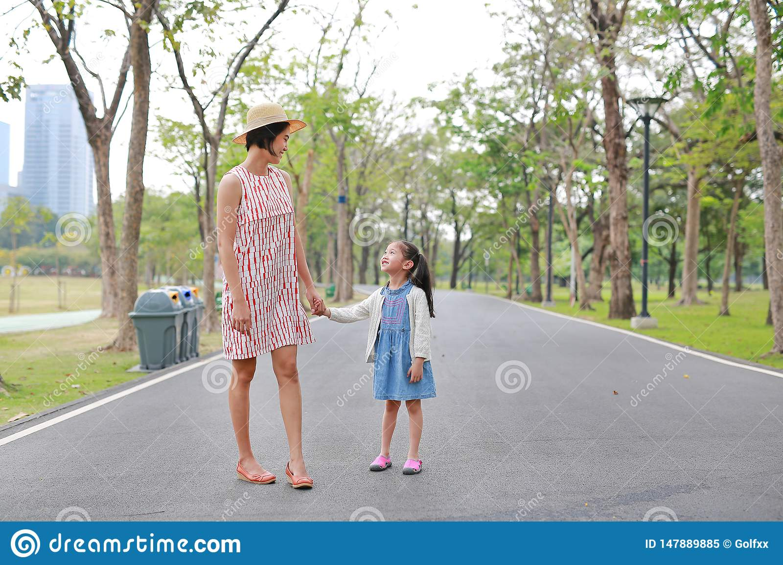 Mom and daughter holding hands in the outdoor nature garden