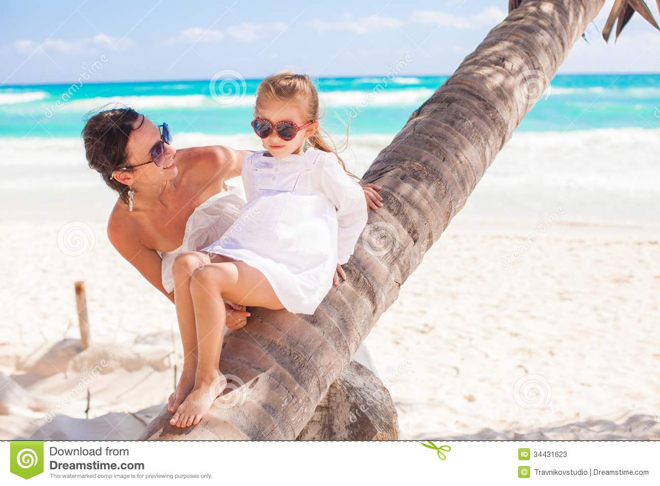 Mom and daughter on a palm tree enjoying vacations stock for Mother daughter vacation destinations