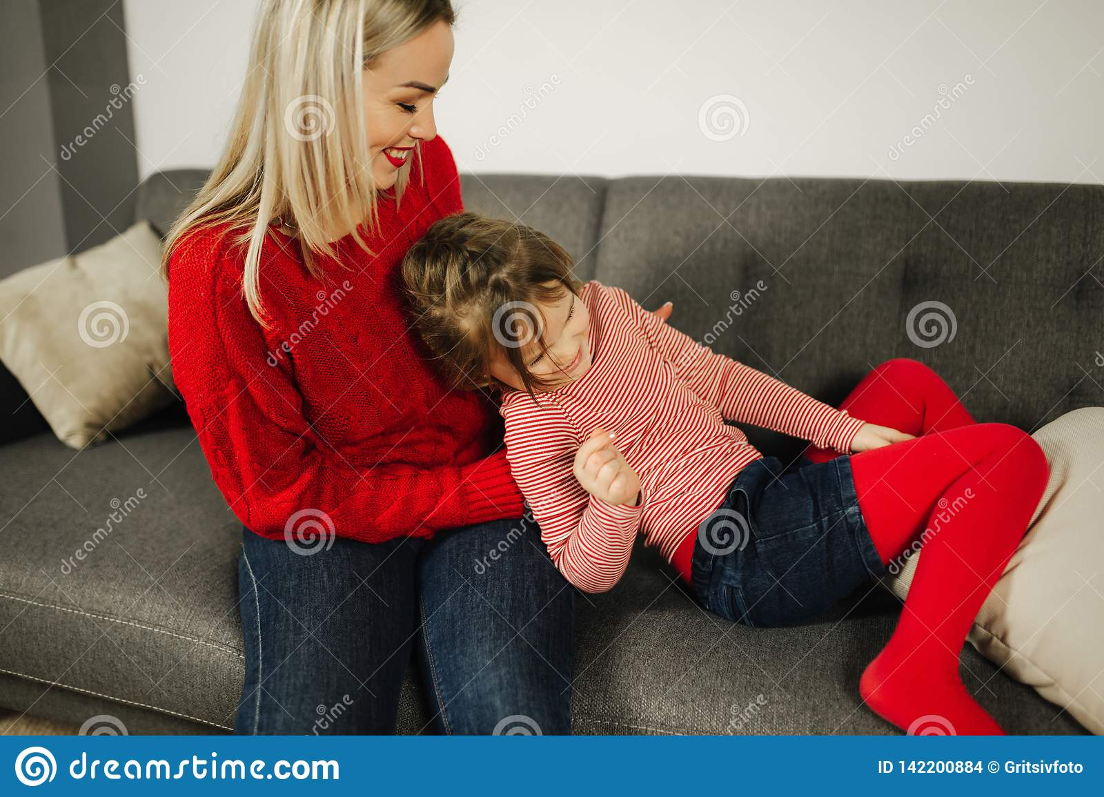 Mom and daughter play at home. Little girl tickle her mother. Happy family spend time together. Blond hair woman