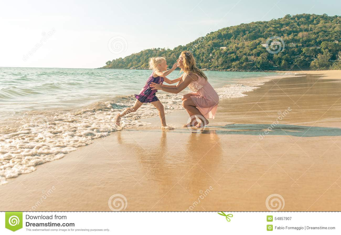 Mom and daughter playing on the beach