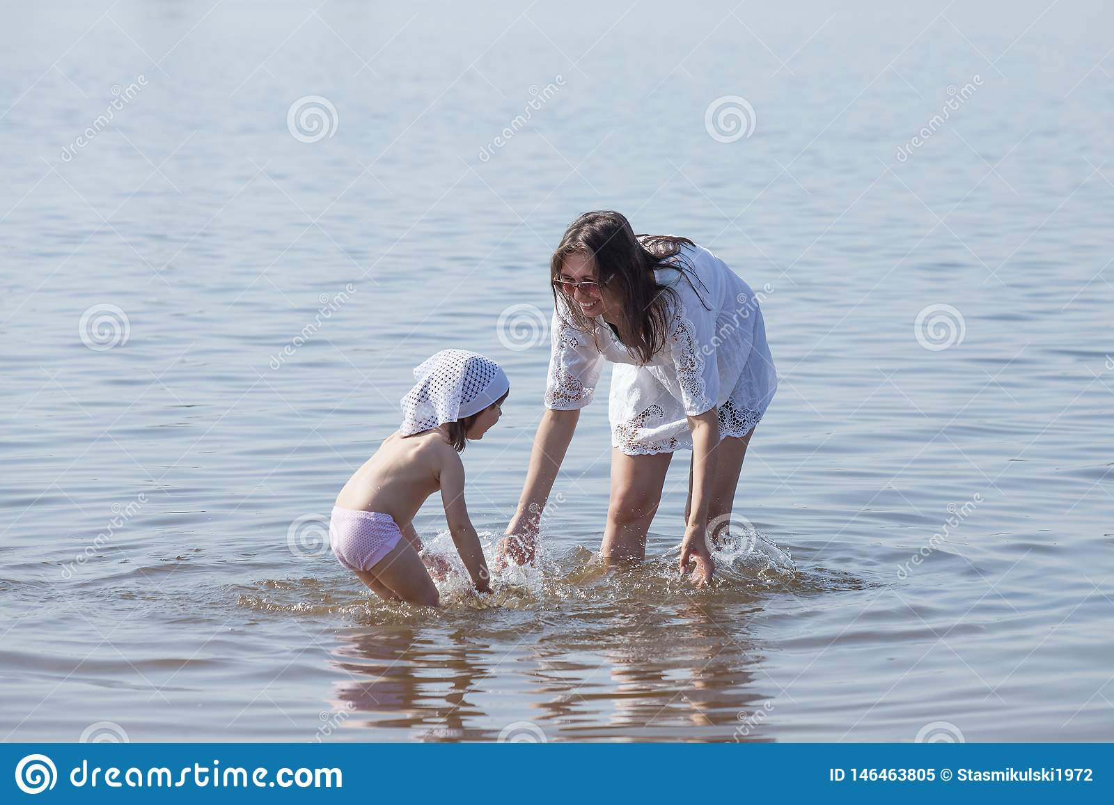 Mom and daughter are playing in the river