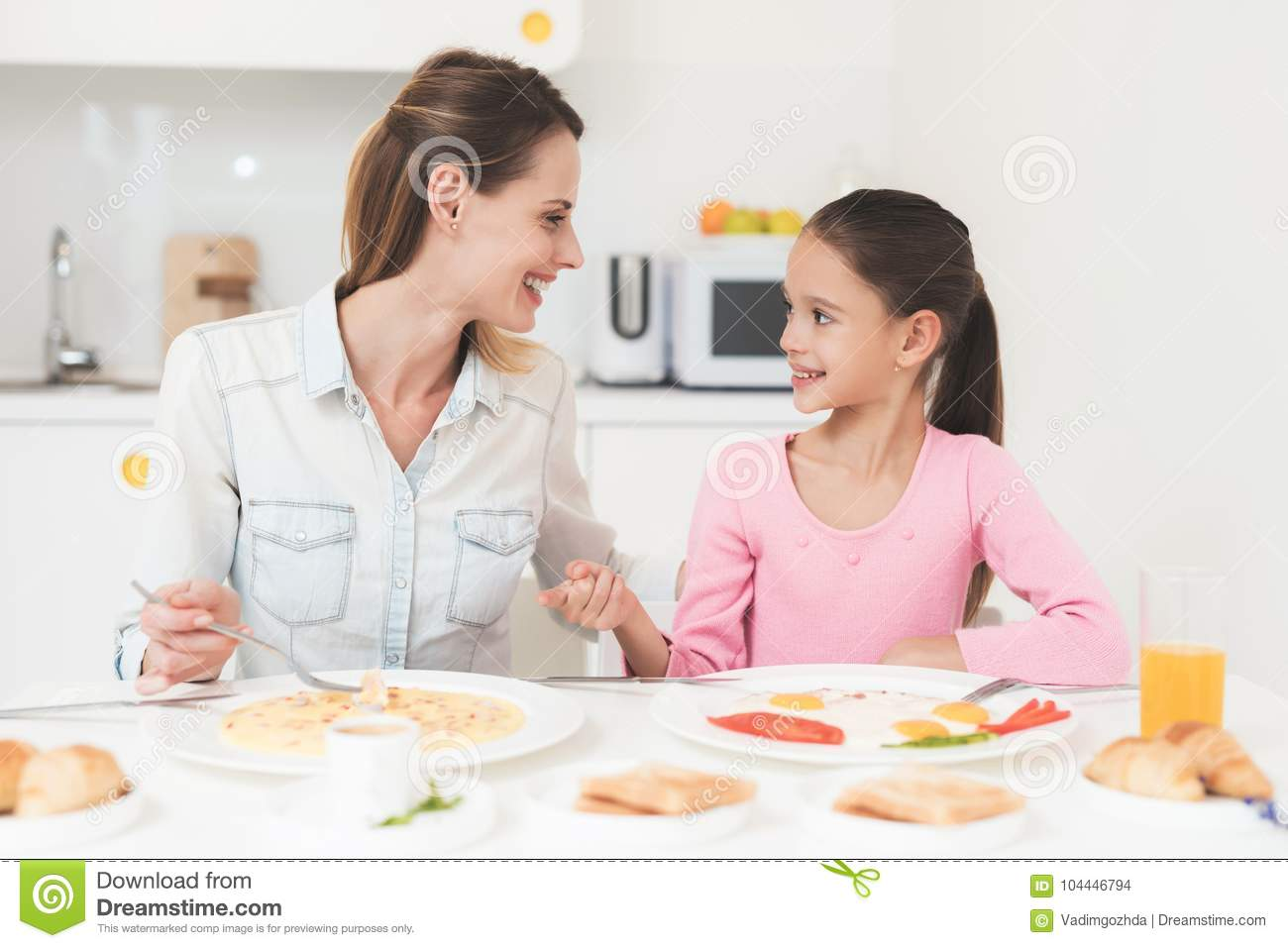Mom And Daughter Are Sitting In The Kitchen And Having Breakfast ...